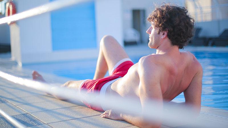 プールサイドで日に焼ける男性