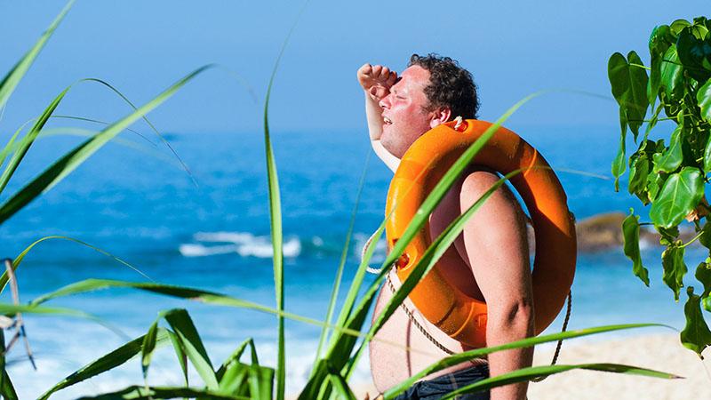 海辺で太陽の紫外線で日に焼けた中年の浮き輪を持った男性