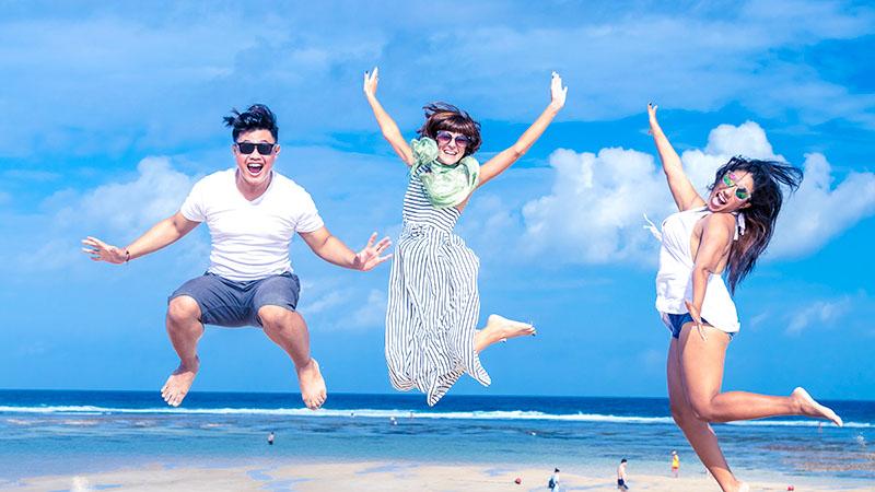 砂浜で紫外線を浴びながらジャンプする男女