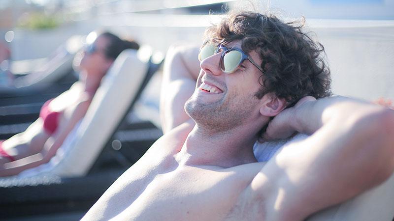 ビーチサイドで休日を楽しむワキのムダ毛をケアした男性