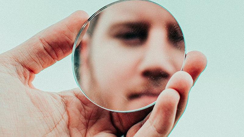 鏡に映った顔を見る男性