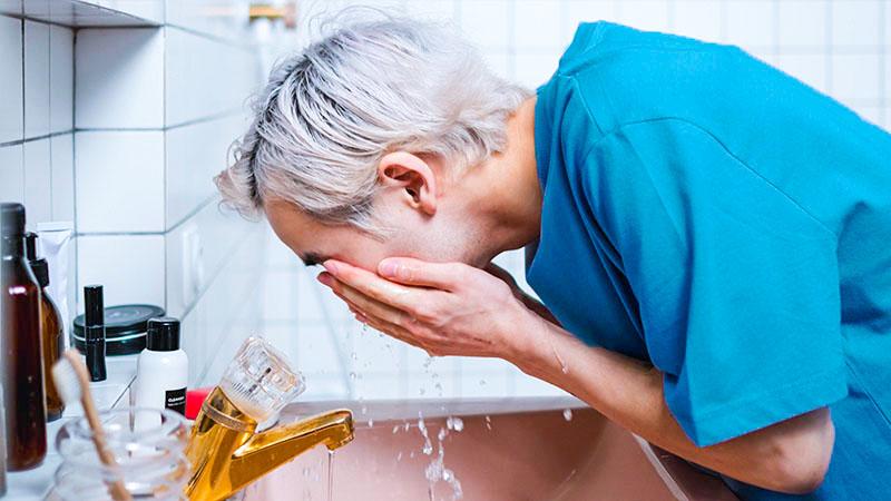 洗顔料で顔を洗う男性