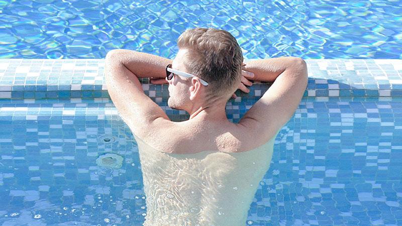 夏のプールで紫外線を浴びる男性